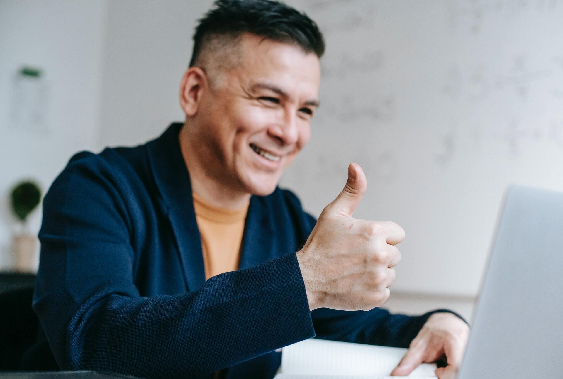 Un profesor hace con la mano el señal de OK durante una clase virtual
